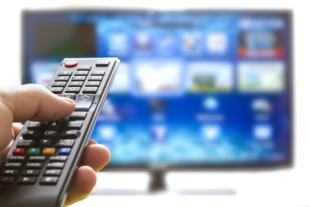 Television remote control changes channels thumb on the blue TV screen