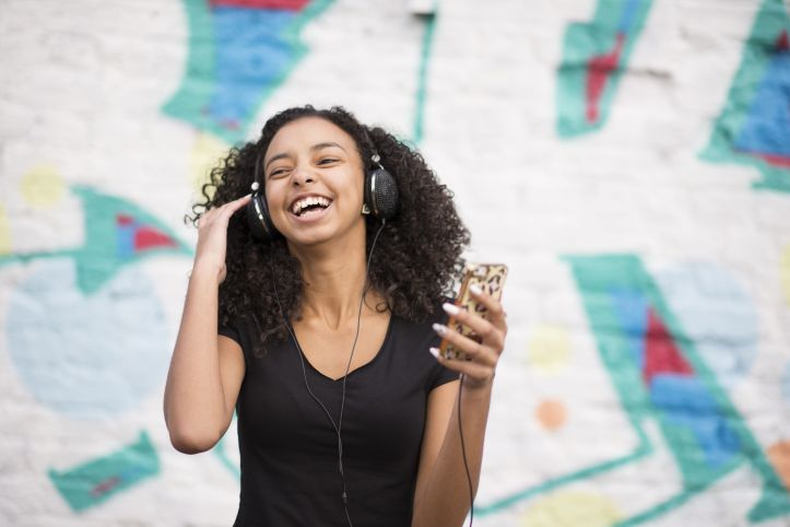 teenager-listening-to-mp3-player-against-wall-with-graffiti-548556465-57cf35153df78c71b69099d7.jpg